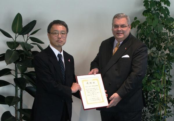 エイボン・プロダクツのエドワード・ホール社長(右)に 感謝状を渡す日本対がん協会・坂野康郎事務局長